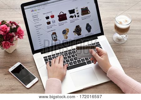 Alushta Russia - October 20 2016: Woman with MacBook and iPhone Internet shopping service eBay on the screen. MacBook and iPhone was created and developed by the Apple inc.