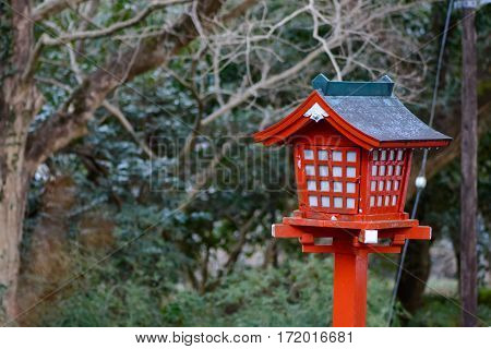 A traditional red wooden lantern with trees of a forest in the background. These lanterns known as toro are in front of Shinto shrines. Japanese architecture and religion concept.