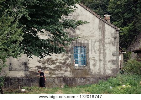 NIKSIC, MONTENEGRO - JULY 25, 2016: old women in profile dressed in black   passes down the side of a large country house