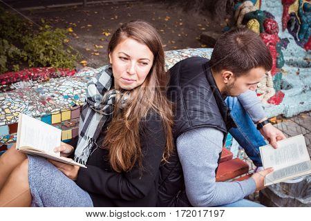 fashion of nice pretty young hipster woman is sitting back to back with a young handsome man and reading a book.