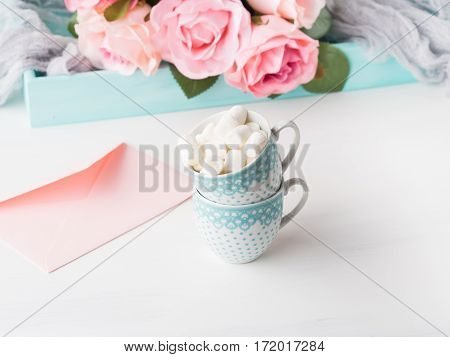 Two coffee cups with marshmallow card for Valentine's or mother woman day. Wedding baby birthday romantic date invitation. Background with roses tray romantic textile