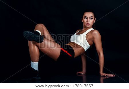 Athletic Young Woman Doing A Fitness Workout Against Black Background. Sporty Woman In Sportswear Wi