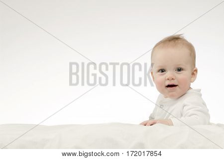Cute smilling 8 month boy in white bodysuite on white background. Studio shot