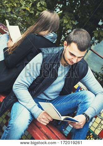 Fashion Of Nice Pretty Young Hipster Woman Is Sitting Back To  With A  Handsome Man And Reading  Boo