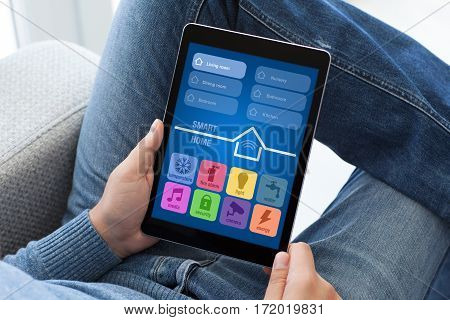 man in jeans sitting on sofa holding tablet computer with app smart home
