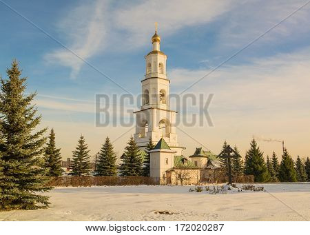 White bell tower in winter fir forest