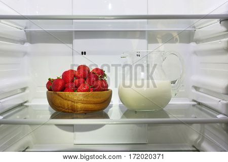 Strawberries in a wooden bowl and a pitcher of milk on a shelf in an empty refrigerator.