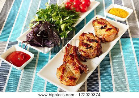 Three slices of grilled pork loin. Next to a plate of herbs and tomatoes.ketchup and mustard.