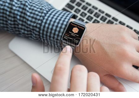 men hands smart touch watch with app tracking delivery package near laptop