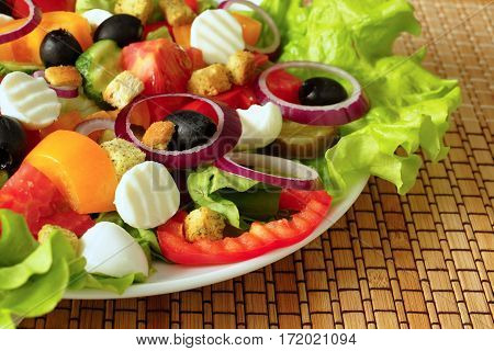 Greek salad on a white plate. Vegetable salad with cheese