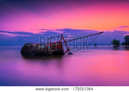 An old shipwreck or abandoned shipwreck Boat capsized on beach in beautiful sunset background Thailand.