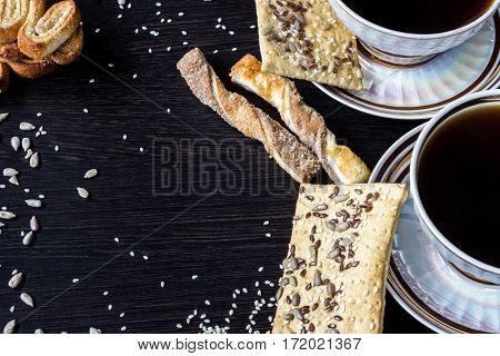 Two cups of coffee with puff pastries with sunflower seeds sesame seeds and flax