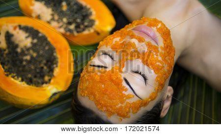 Beautiful caucasian Woman Having fresh Papaya natural facial mask apply. Papaya Peeling. Skin care and Wellness (outdoors). Facial vitamin mask of papaya slices at spa salon. Antioxidant cosmetic