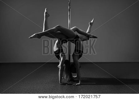 Two Young Flexible Dancer Doing Difficult Acrobatic Tricks With A Pole. Black And White
