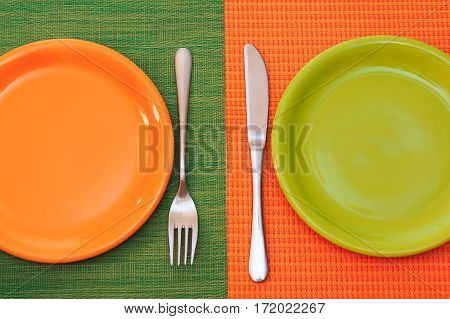 Two empty plates. Orange stands on a green napkin,green on orange  napkin. Fork and knife  near the plates. Top view
