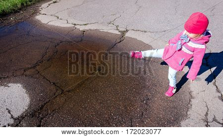 Little Girl In A Pink Coat, Jeans And Boots Walking The Park