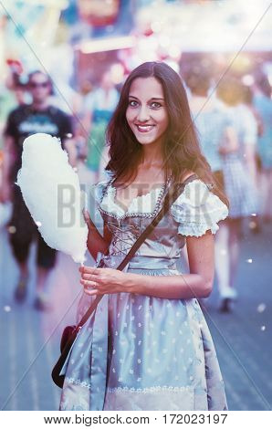Gorgeous young woman in traditional German dress holding and picking at a wad of cotton candy