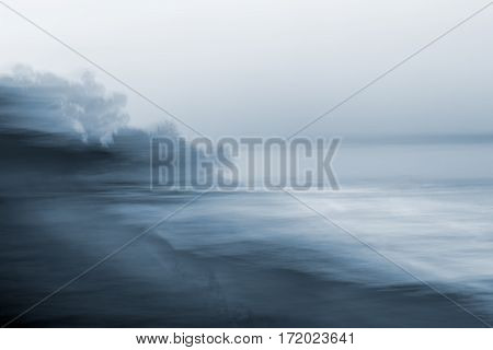 A monotone blurred seascape made using a long exposure combined with horizontal panning motion.