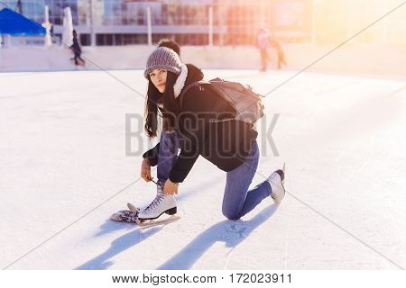 Beautiful Girl Having Fun In Winter Park, Ties The Laces On The Skates At Ice Rink. Enjoying Nature,