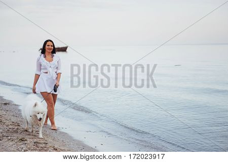 Beautiful brunette woman on the beach with a dog walking.