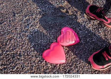 Two Hearts And The Child's Feet In Sneakers On Sand.