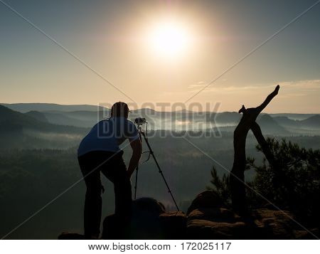 Photographer Takes Photos With Camera On Peak Of Rock