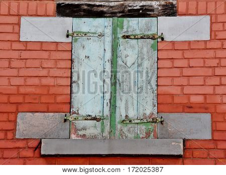 Close up of red brick wall with window and closed wooden shutters