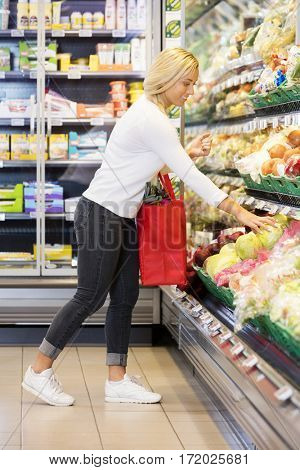 Woman Buying Cabbage In Supermarket