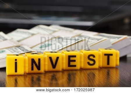 Concept investments, word made by letter blocks. Stack of money american hundred dollar bills