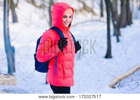 Woman Walking Alone In Winter Forest With Backpack