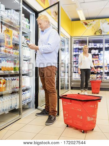 Customer Using Mobile Phone At Refrigerator In Supermarket