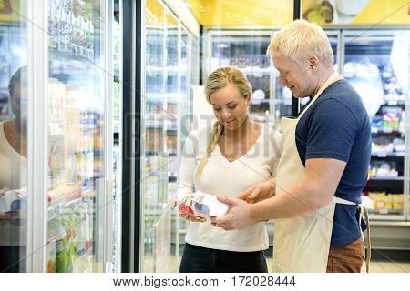 Salesman Showing Drink Packet To Customer In Grocery Store