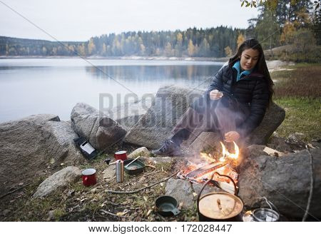 Woman Sitting Near Bonfire On Lakeshore During Camping