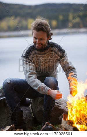 Man Warming Hands By Bonfire On Lakeside Camping