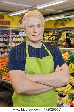 Salesman With Hands Folded Standing In Grocery Store