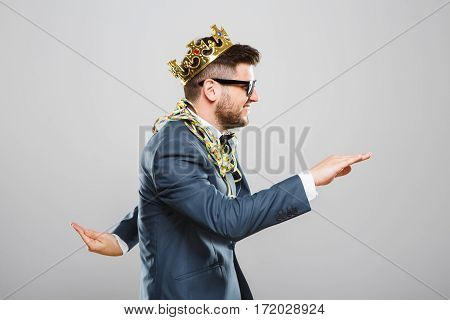 Stylish young man in suit with bow and sunglasses. Wearing crown, confetti on shoulders. Having fun, dancing, smiling. Outrageous, fancy look, eccentric. Waist up, profile, studio indoors