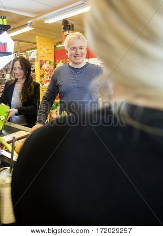 Customers Smiling At Checkout Counter