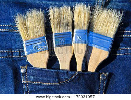 Paintbrush in the pocket of blue jeans