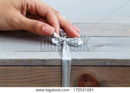 Female Hand Unties The Ribbon On Gift Wooden Box