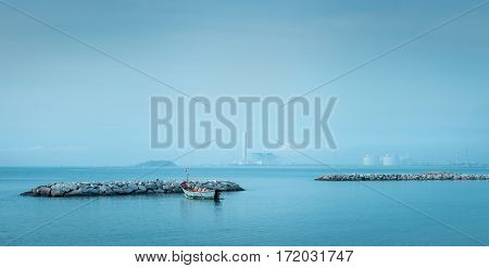 small fishing boat floating parked behind a reef in morning.