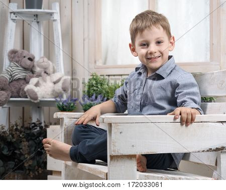 Happy little boy sitting on a chair. Bright children's room. Portrait of a child smile emotion