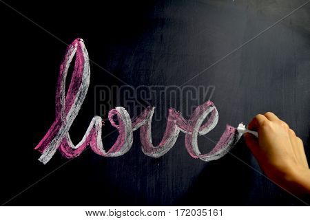 Image of a hand writing love word by chalk on blackboard.