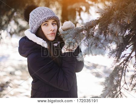 Beautiful Girl In A Knitted Hat And Mittens In The Winter Snowy Forest. Woman Near A Tree In The Win