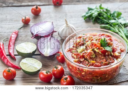 Bowl of salsa with ingredients on the wooden background