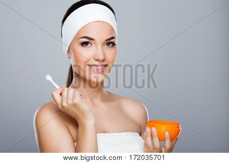 Woman with white headband holding orange cream. Model looking at camera and smiling, having cream on applicator. Head and shoulders. Beauty salon, studio, indoors, grey background