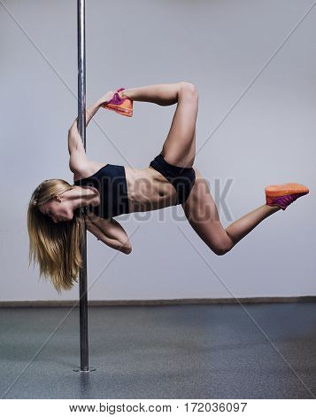Beautiful Young Woman Holding A Pose In A Pole Fitness Class