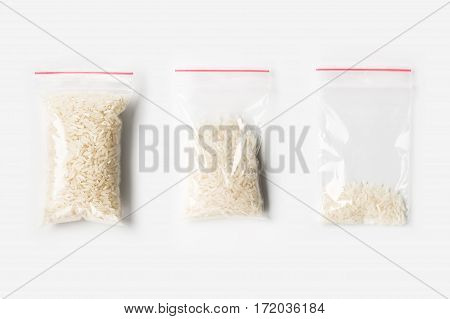 Set Of Three Empty, Half And Full Plastic Transparent Zipper Bag With Uncooked White Basmati Rice Is