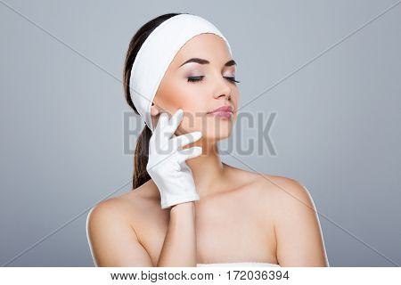 Woman with white headband touching face with hand in white glove. Model with closed eyes. Head and shoulders. Beauty salon, studio, indoors, grey background