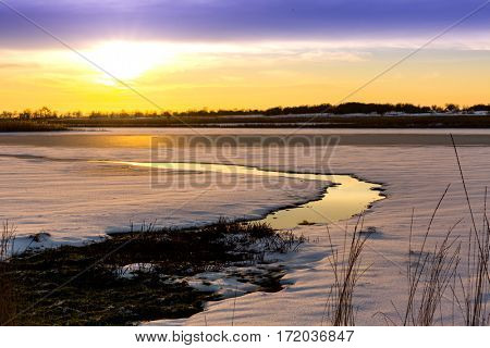 evening landscape over small river in winter time