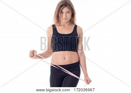 Charming athletic girl who looks forward and holding a measuring tape measure in his hand